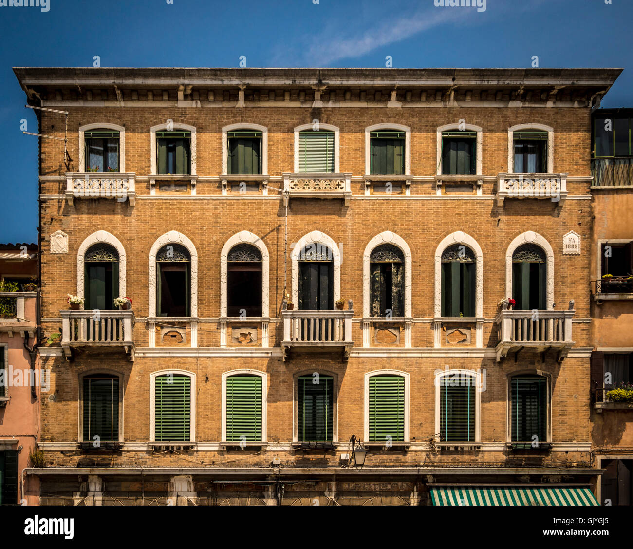 Traditional brick building with venetian blinds at the arched windows. - Stock Image