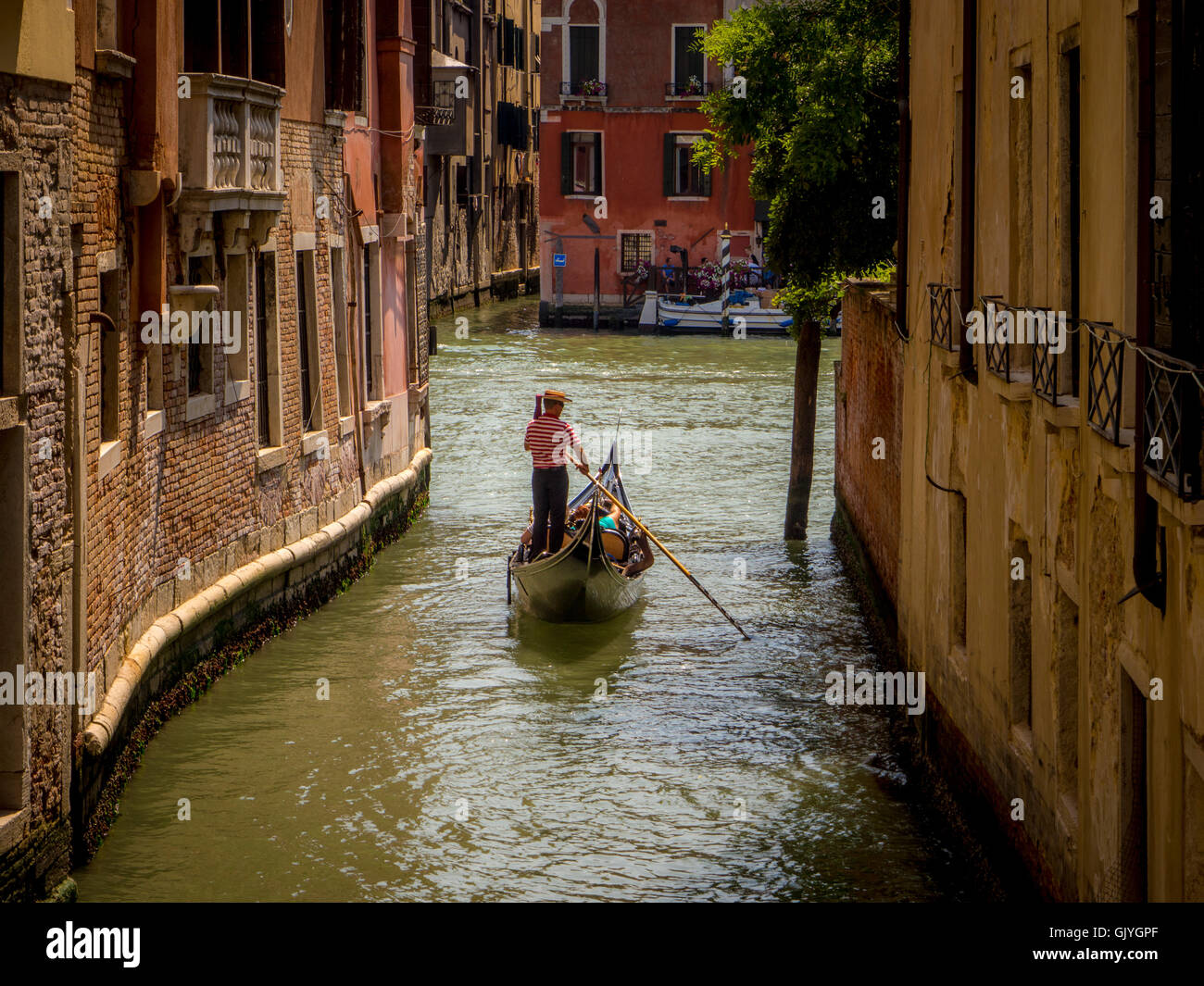 79d5a4fcb57 Single gondolier wearing a traditional boater hat and striped top  propelling his gondola along a canal