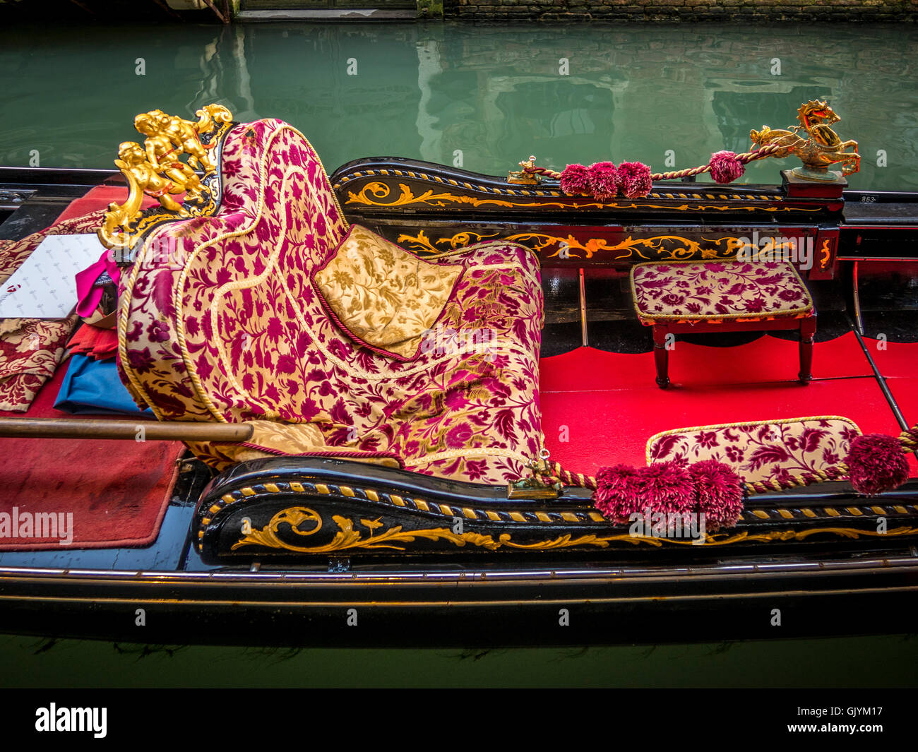 Ornate upholstered seats in a moored gondola. Venice, Italy. - Stock Image