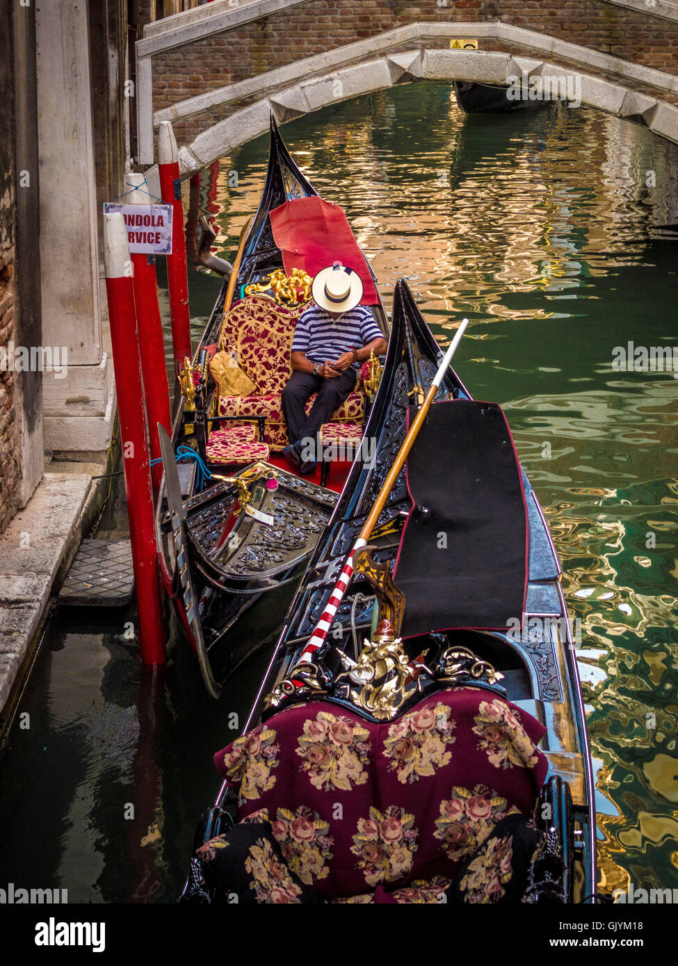 8f83b2d0957 Gondolier wearing traditional striped top and straw boater hat sitting in  his boat sending a text