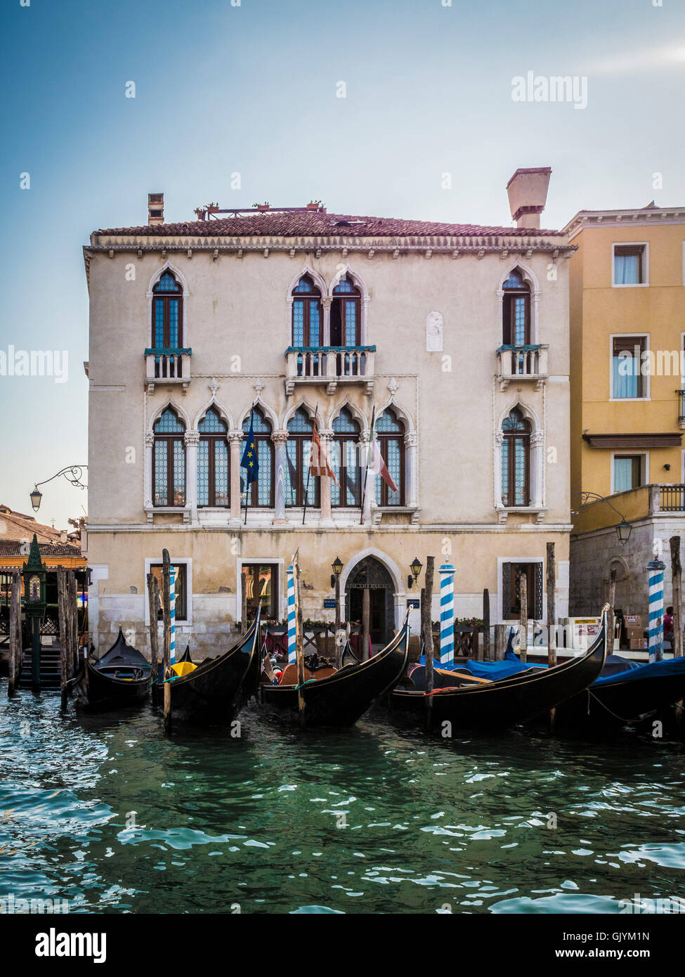 Moored gondolas in front of a traditional venetian building. Venice, Italy. - Stock Image