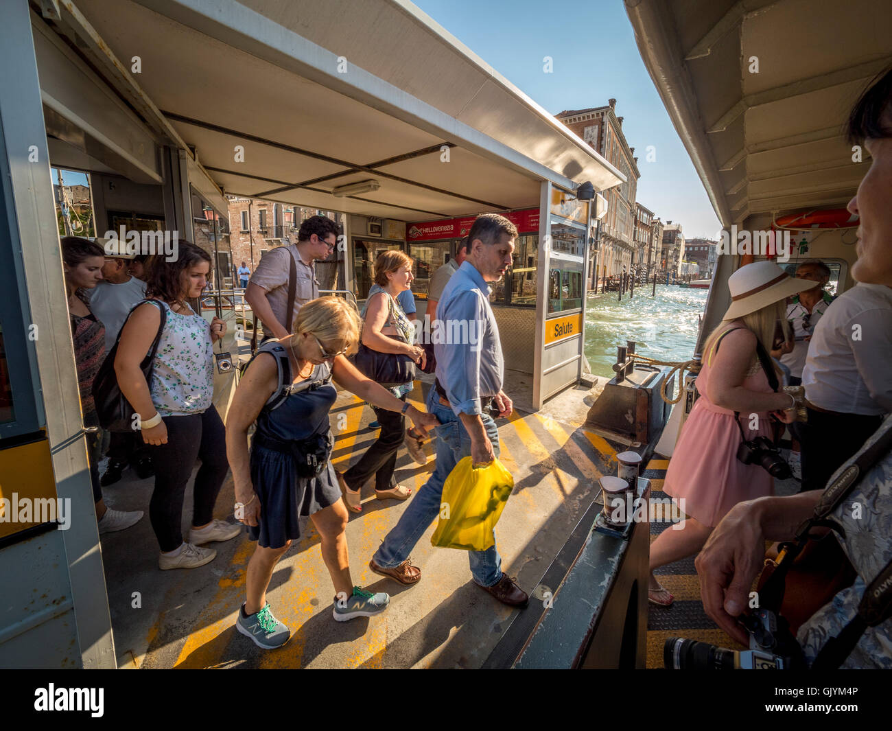 Passengers boarding the water bus or vaporetto, on the Grand Canal in Venice, Italy. - Stock Image