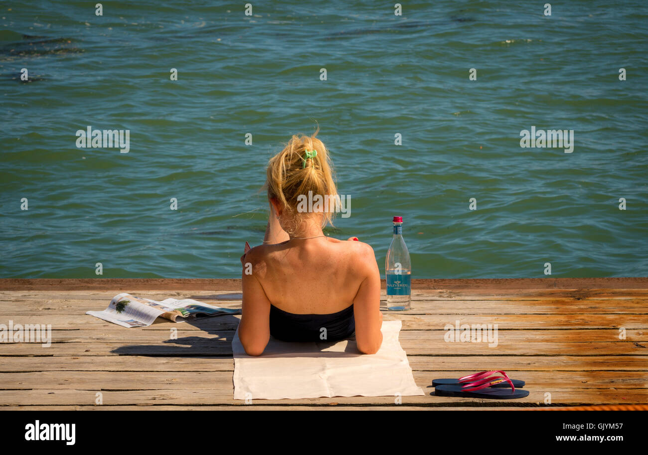 Young female reclining on a wooden jetty on the Canale della Giudecca. Vence,Italy. - Stock Image