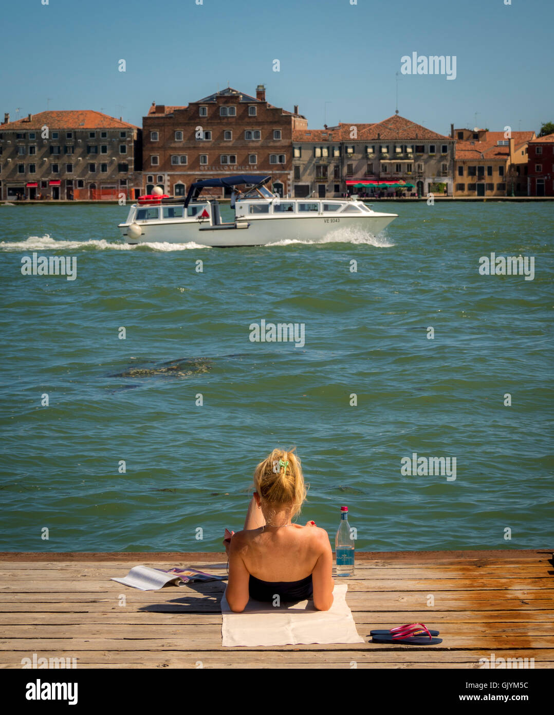 Young female reclining on a wooden jetty on the Canale della Giudecca, with a boat and the island of Giudecca in - Stock Image
