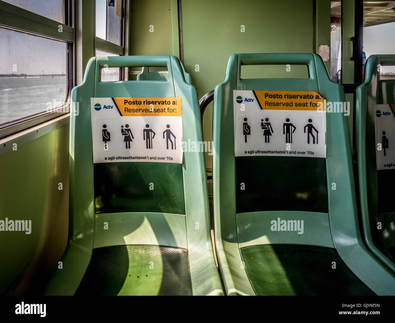 Seats reserved for the elderly, infirm and pregnant women, on a vaporetto, Venice, Italy. - Stock Image