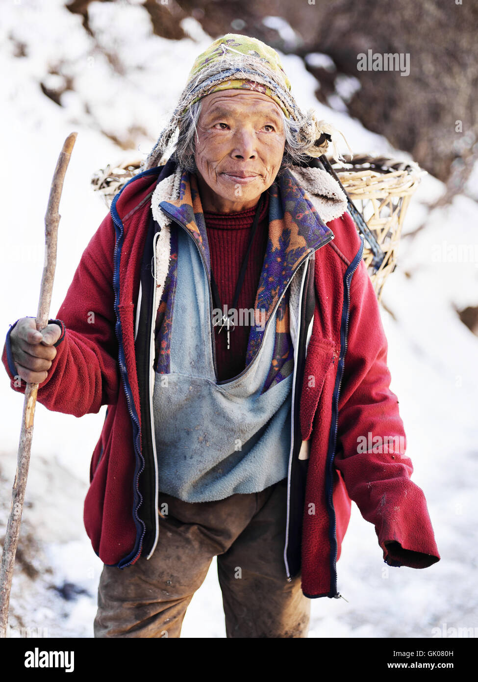 Man carrying goods in a homemade basket backpack across the Himalayas near Pheriche, Nepal. - Stock Image