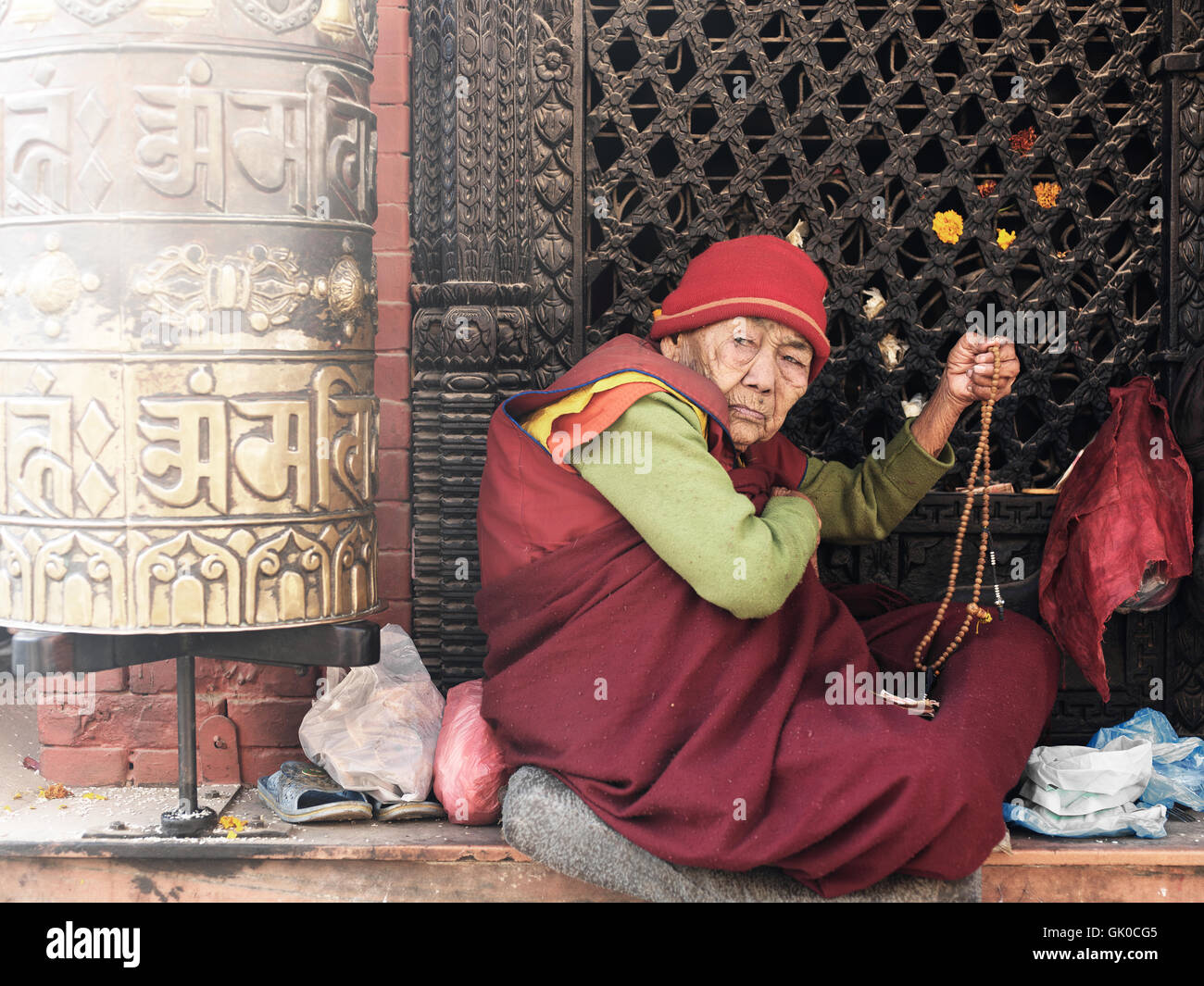 Sitting outside the Boudhanath Pagoda in Kathmandu, Nepal. - Stock Image