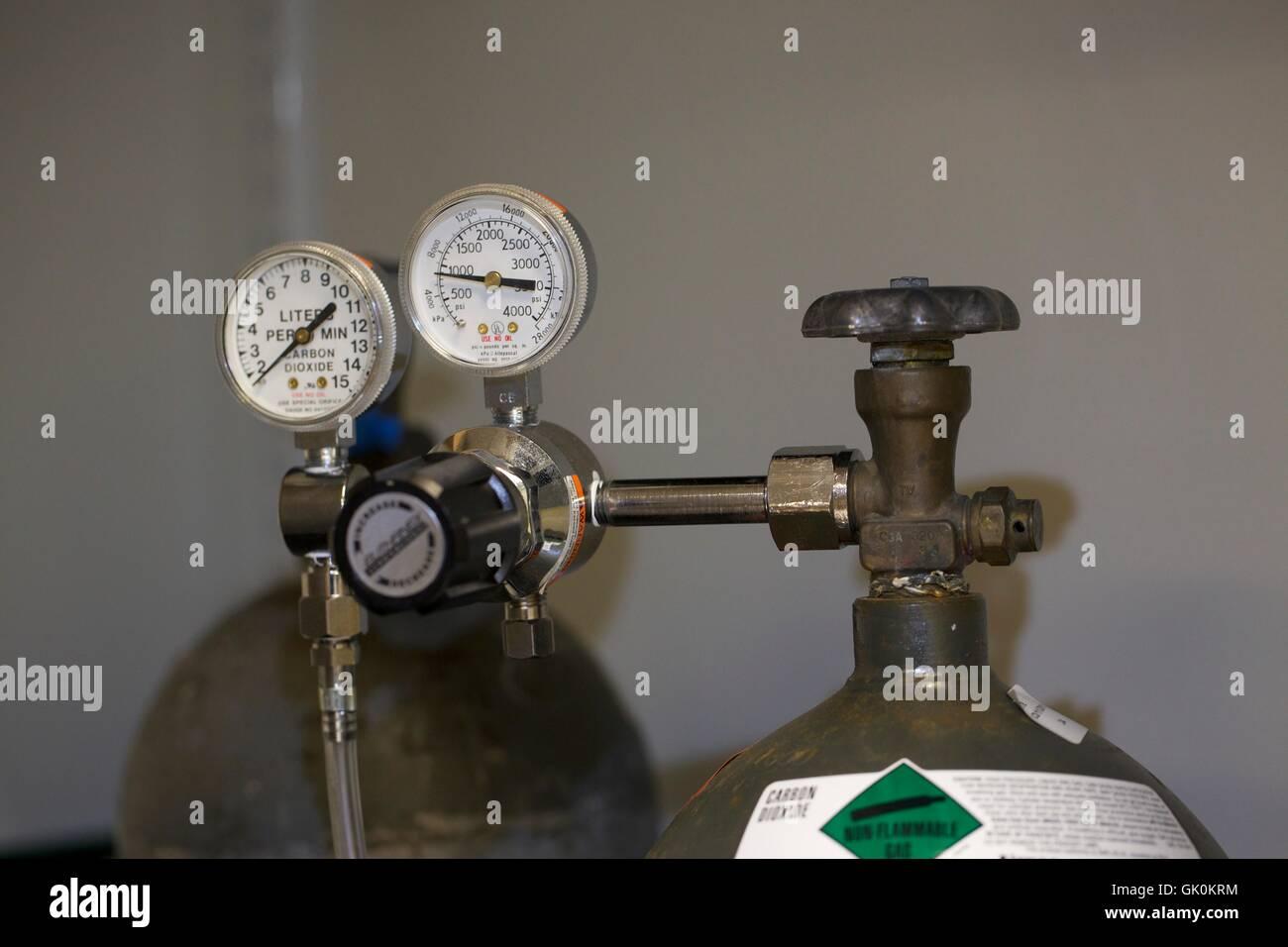 Pressure gauge and valve on carbon dioxide tank. - Stock Image