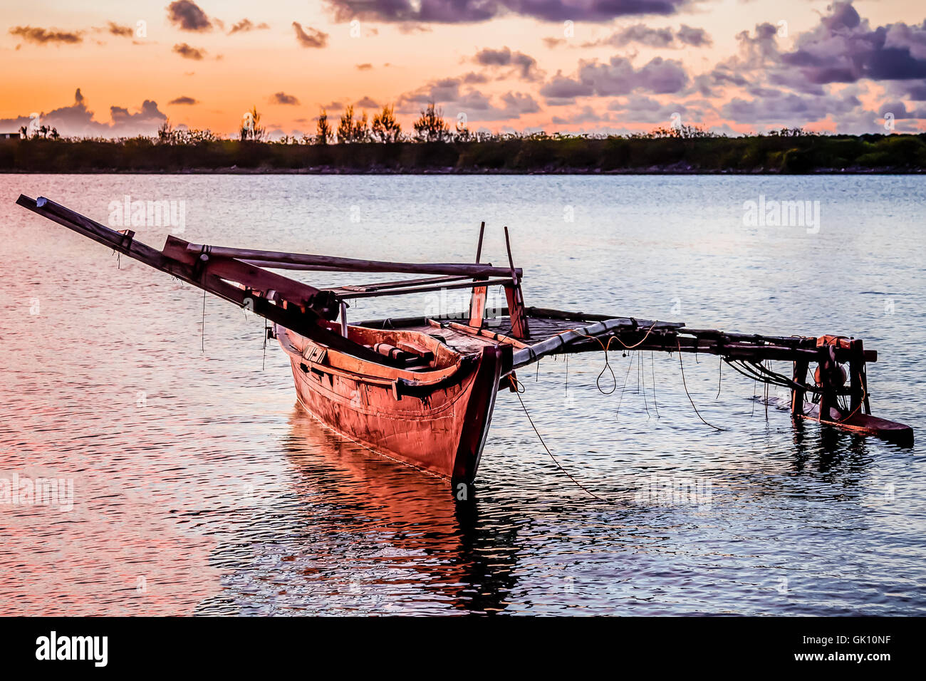 A wooden Micronesian canoe anchored in the bay at sunset. - Stock Image