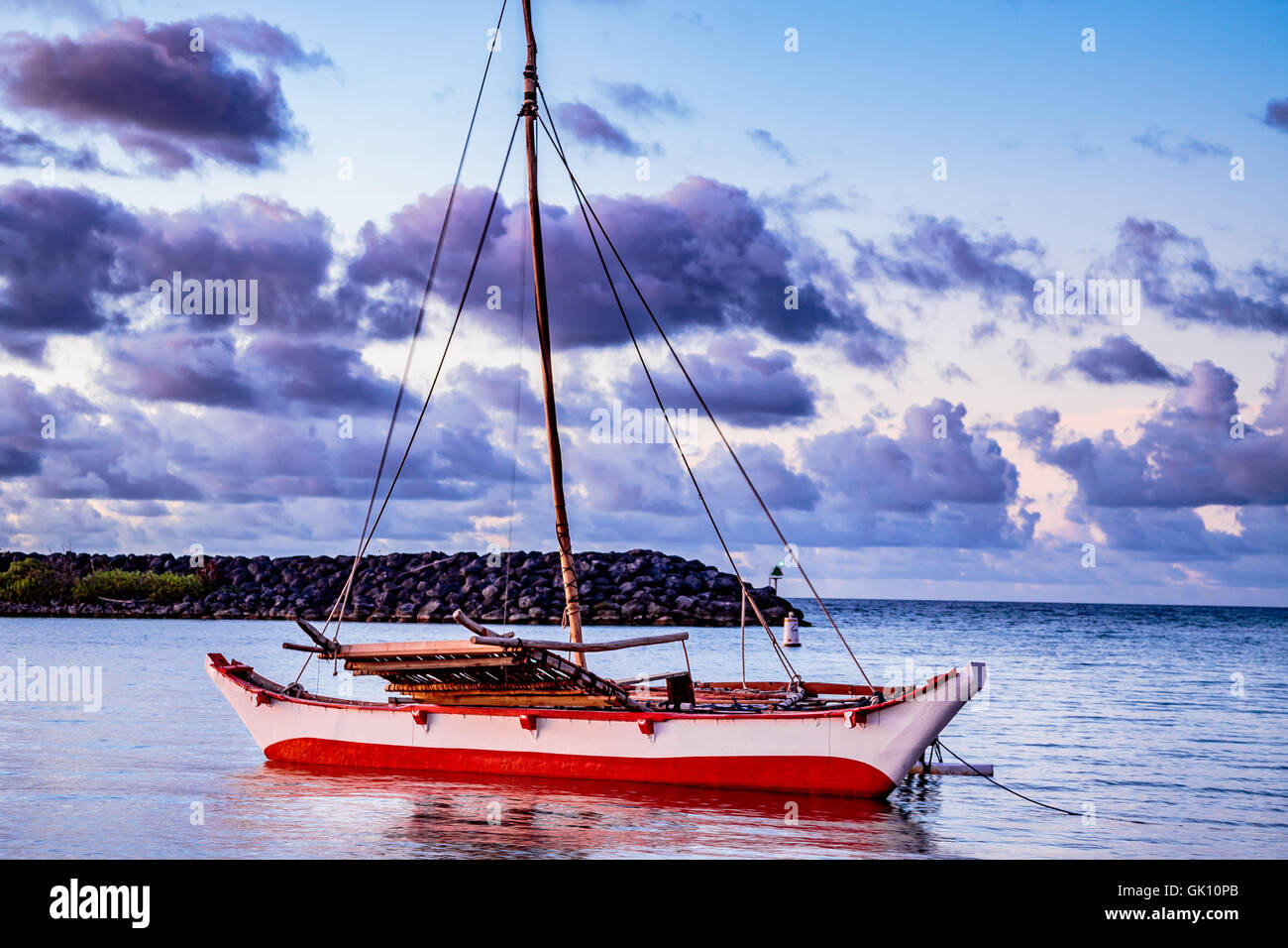 A micronesian tribal catamaran at anchor at the mouth of the bay. - Stock Image