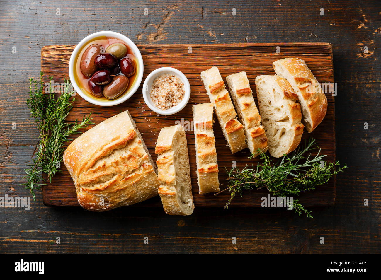 Fresh Ciabatta bread cut in slices on wooden cutting board with olives and herbs on rustic wooden background - Stock Image
