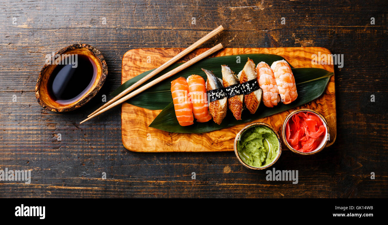 Nigiri Sushi Set on bamboo green leaf on olive wood board with soy sauce on wooden background Stock Photo