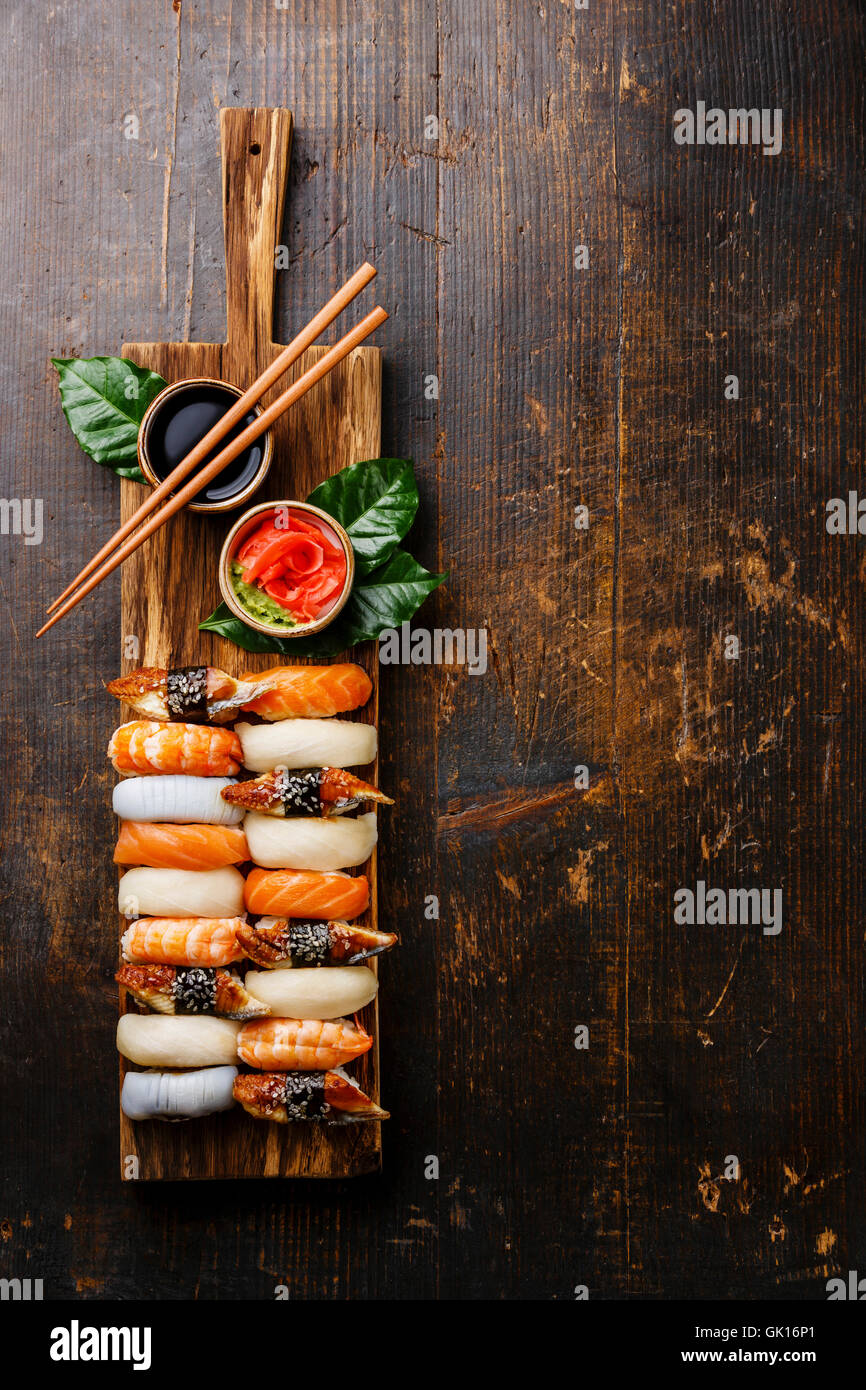 Nigiri Sushi set on wooden serving board with copy space on dark wooden background - Stock Image