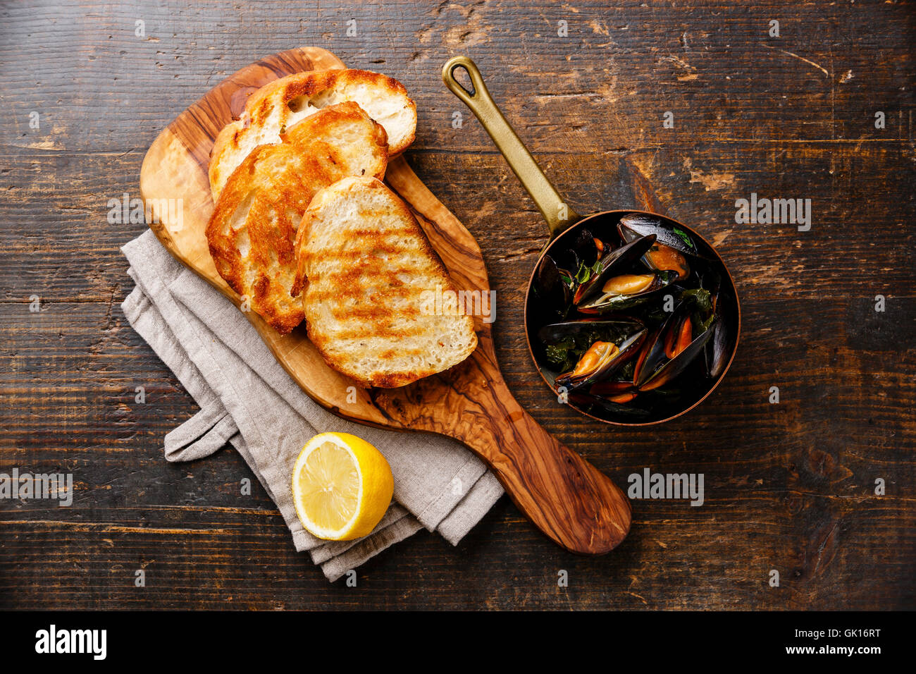 Mussels in copper pot, bread toasts and lemon on wooden background Stock Photo