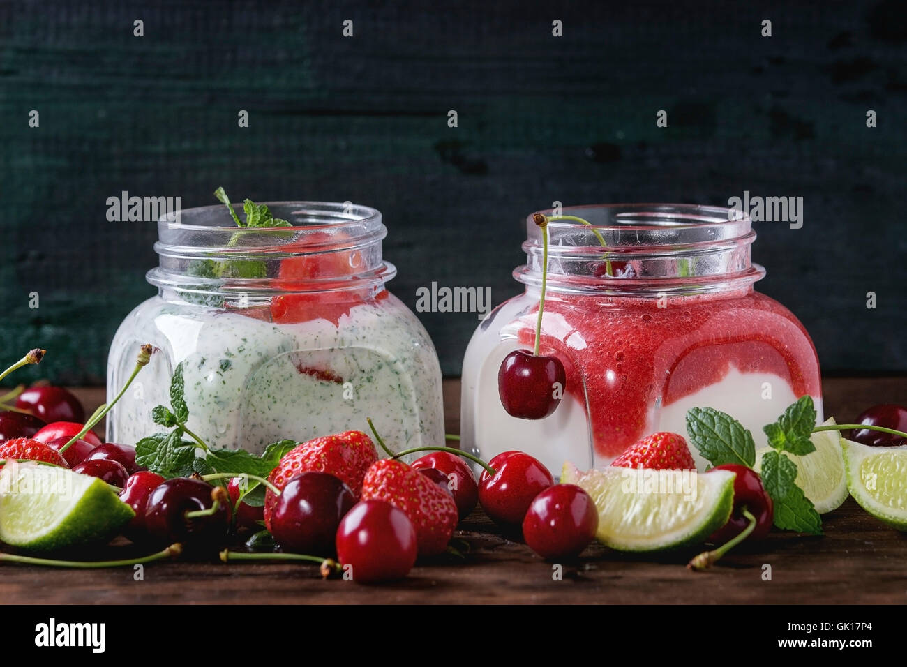 Two Square glass jars with homemade yogurt with mint, strawberry puree, cherry and chia seeds served with fresh Stock Photo