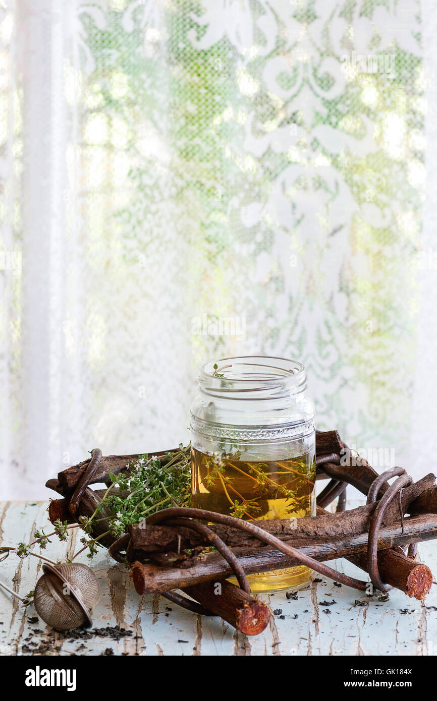Glass jar of hot herbal tea with bunch of fresh thyme, served with vintage tea-strainer on old wooden stool with - Stock Image