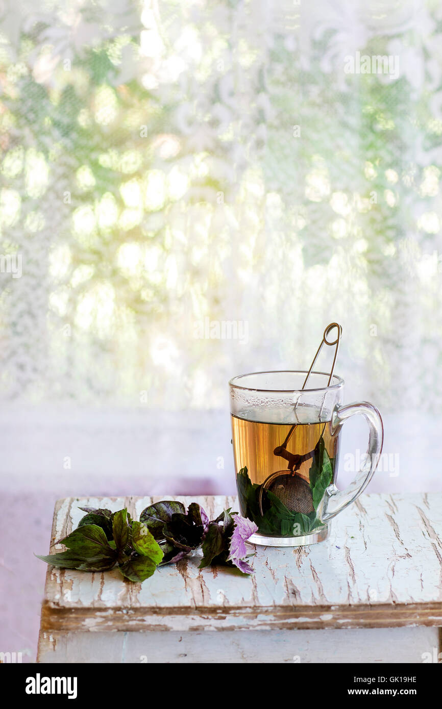 Glass cup of hot herbal tea with bunch of fresh violet basil, served with vintage tea-strainer on old wooden stool - Stock Image