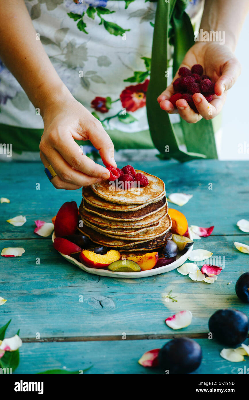 Girl putting raspberries on the top of pancakes - Stock Image