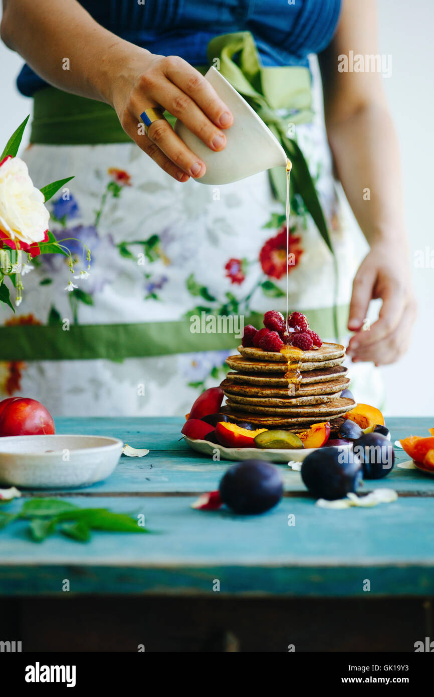 Girl with flower apron pours honey over pancakes - Stock Image