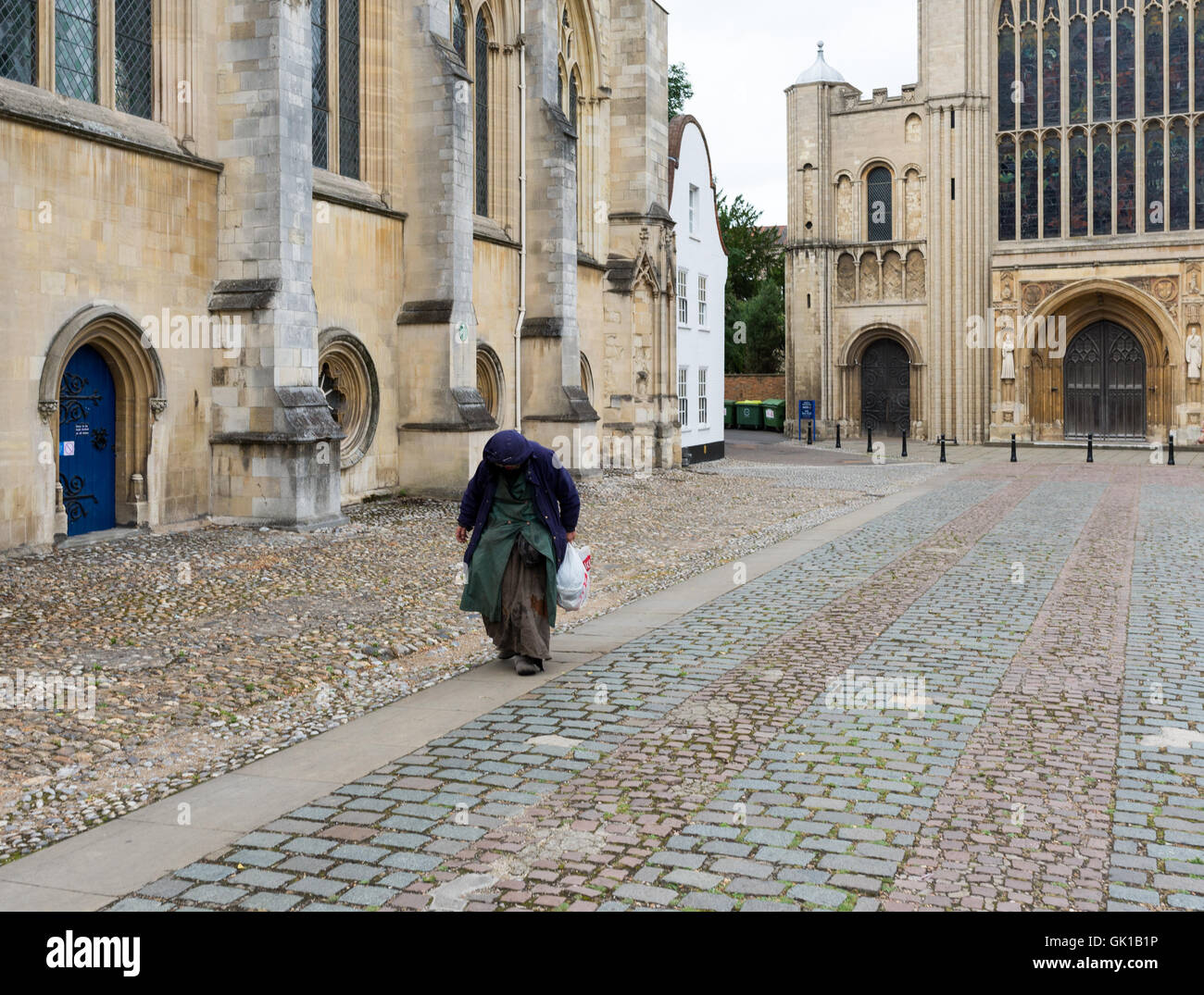 Bag lady at the cathedral. A down and out tramp walking through cathedral grounds to her next doorway sleeping spot. - Stock Image