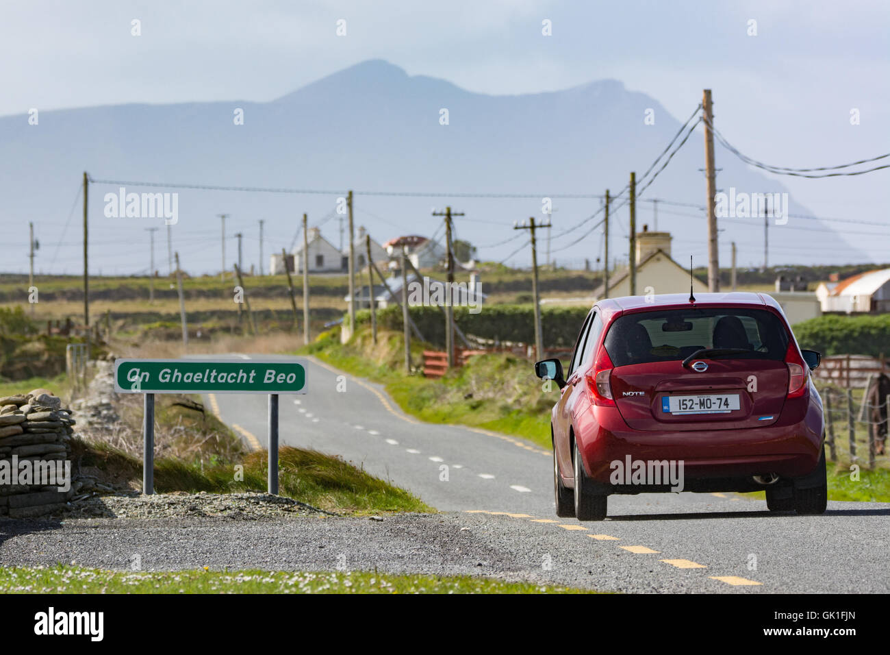 Car drives past An Ghaeltacht Beo sign (living Irish-speaking region) near Belmullet in Mayo on the west coast of - Stock Image
