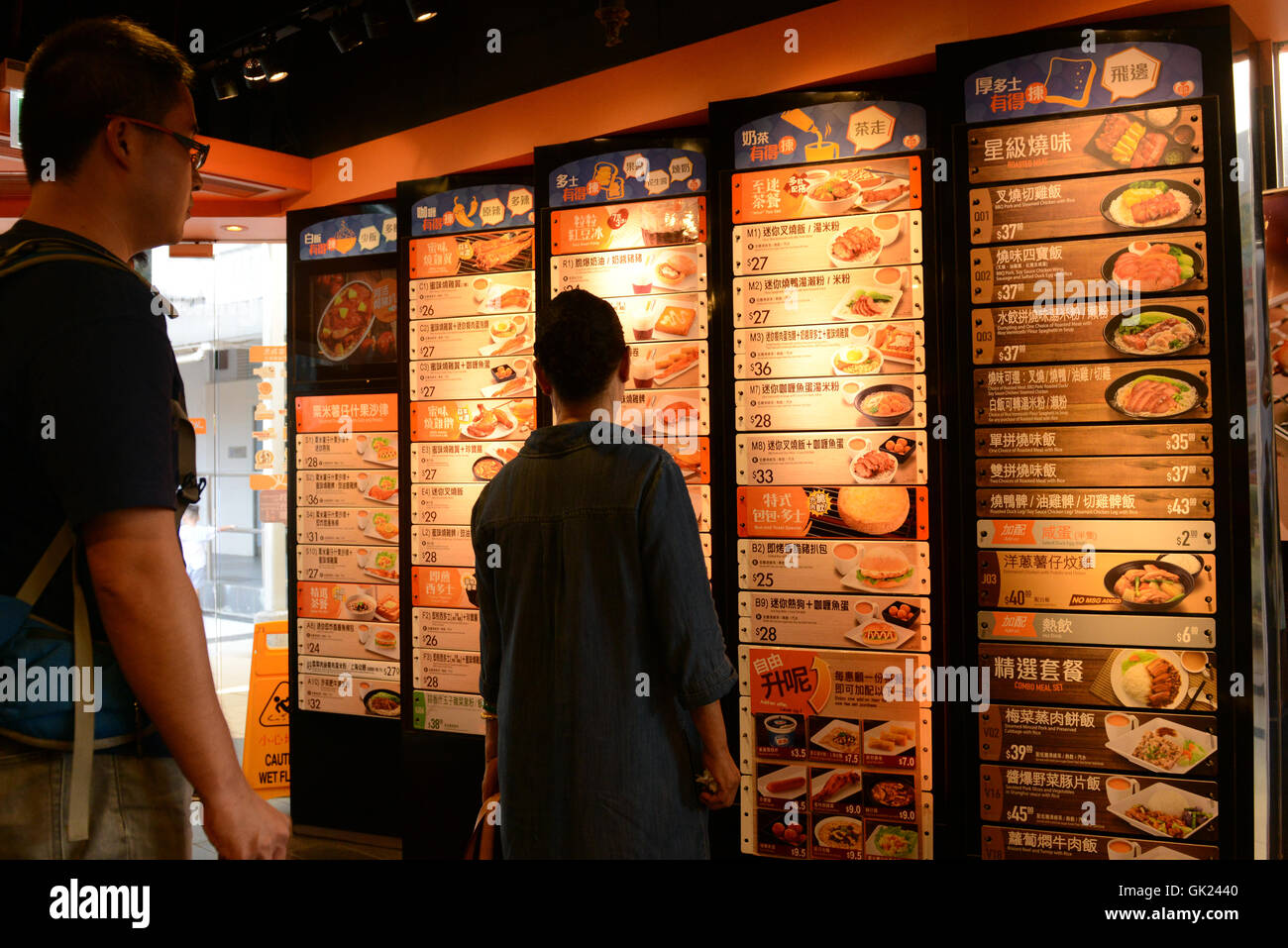 Hong Kong style fast food restaurants. The menu is displayed on a wall at the entrance, customers order at the cashier. Stock Photo
