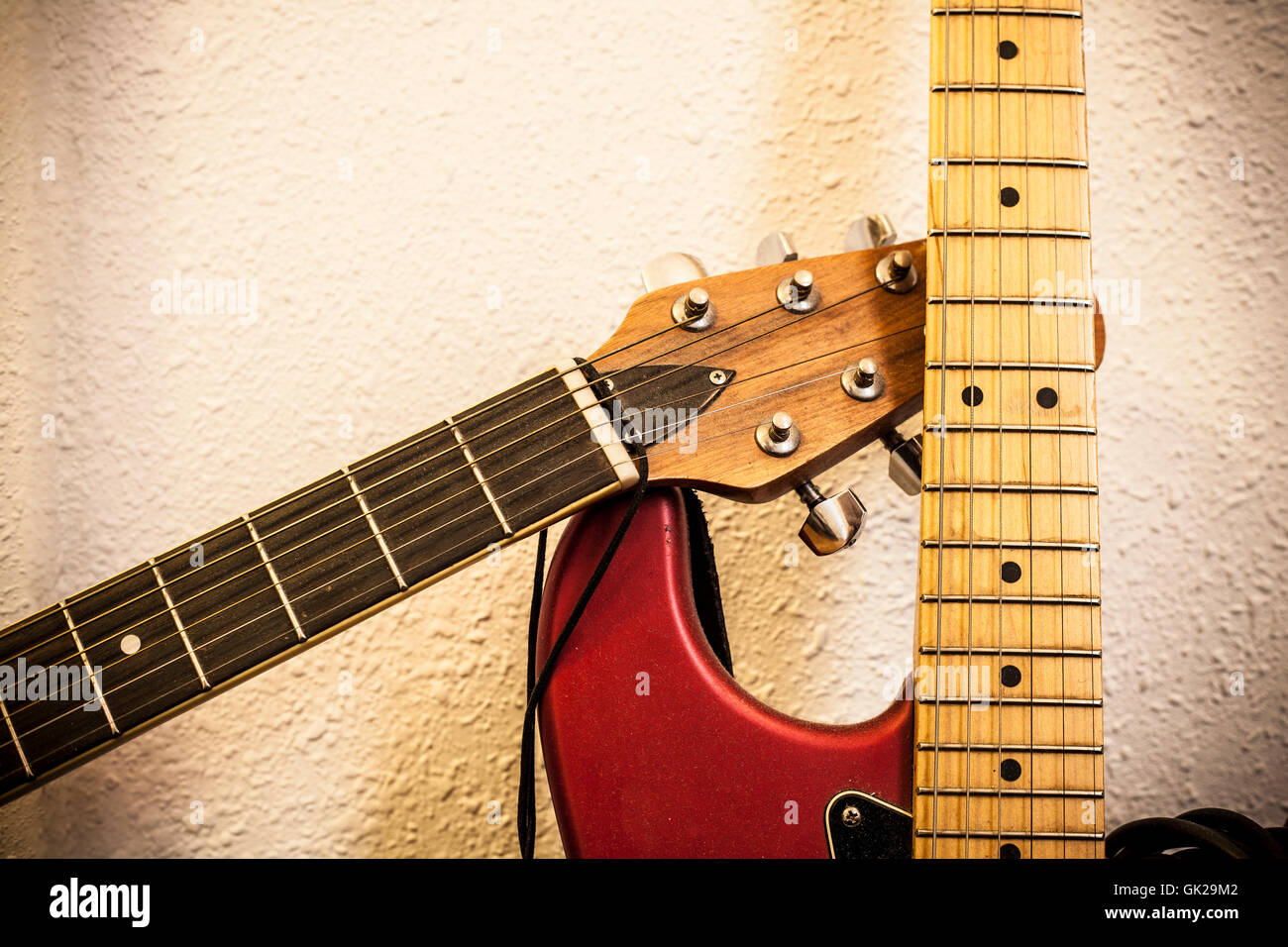 Closeup of two guitar necks over wall background. Vintage filtered - Stock Image