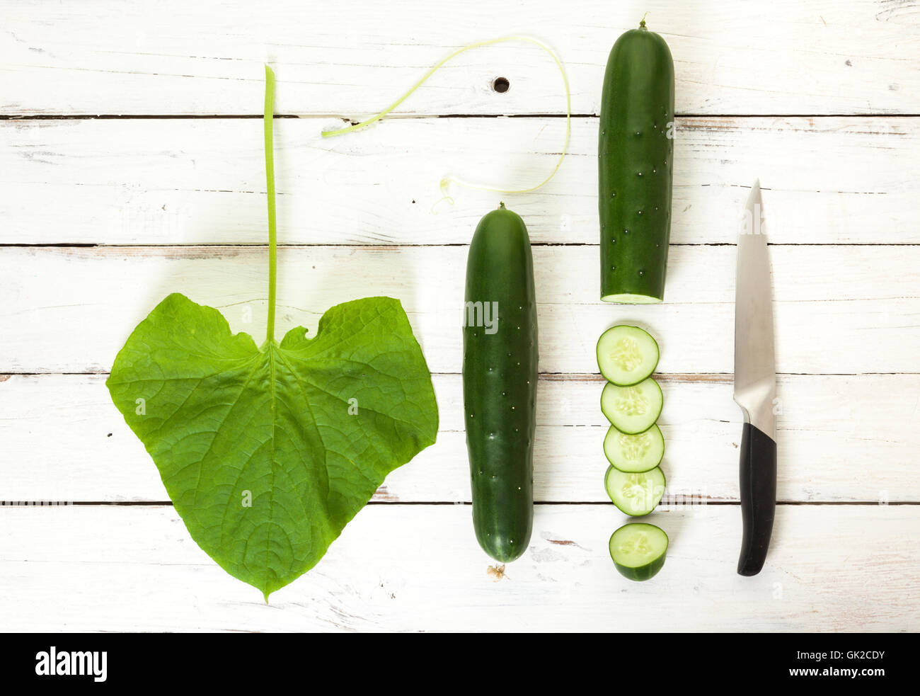Flat lay still life of cucumbers with their leaf and vine, slices and chopping knife - Stock Image