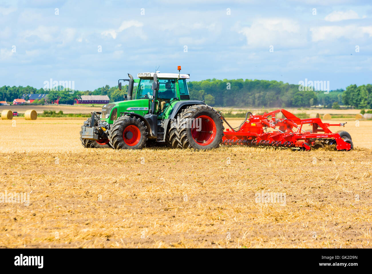 Kalmar, Sweden - August 10, 2016: Farmer disk rolling field with green Fendt 820 tractor. Farmhouse and forest in - Stock Image
