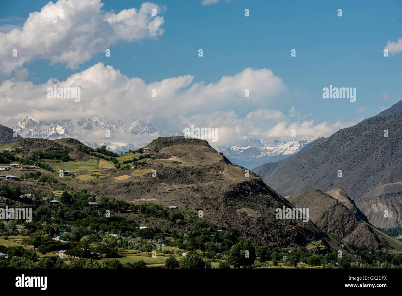 Hill top overlooking the village of Ayun in northern Pakistan, with the mountains of the Hindu Kush in the background - Stock Image
