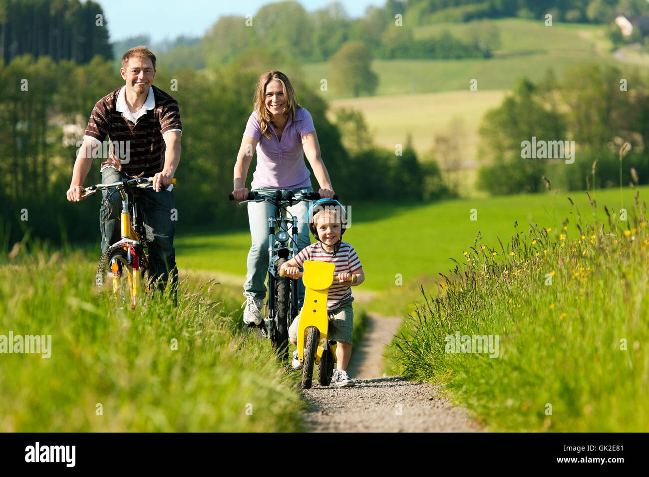 family riding bikes in summer - Stock Image