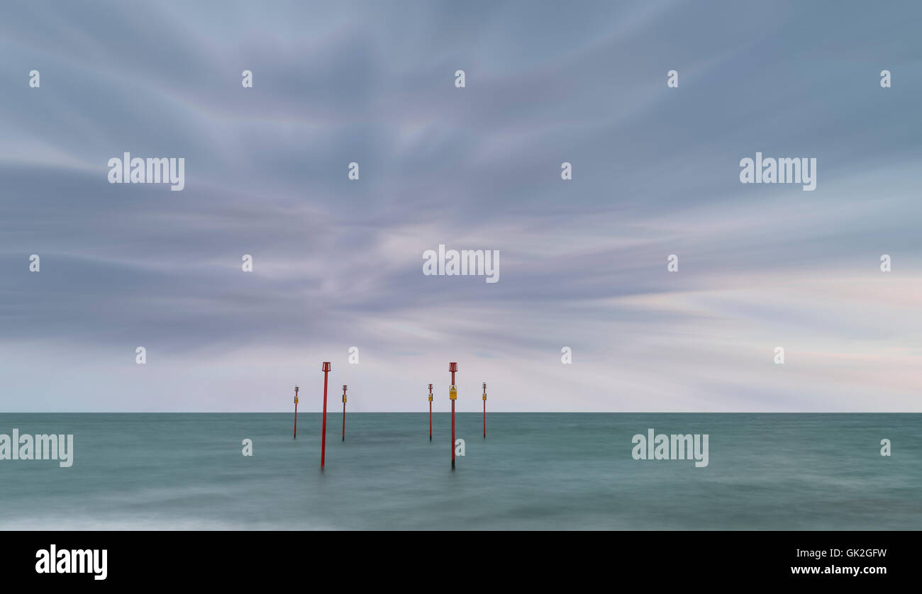 Beautiful vibrant conceptual image of posts in sea standing sentinel against the weather and tide - Stock Image