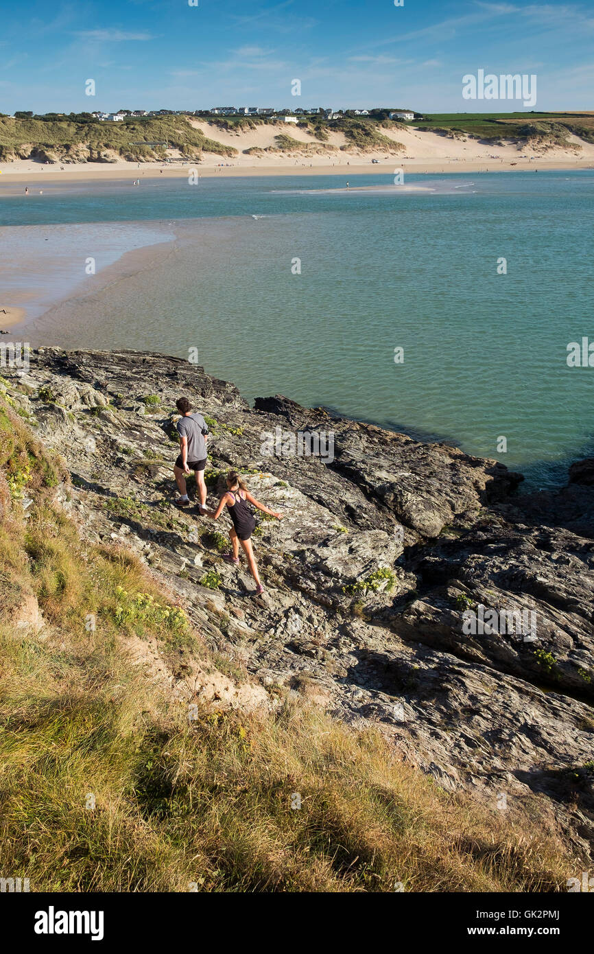 Holidaymakers clamber over rocks on East Pentire Headland in Newquay, Cornwall. - Stock Image