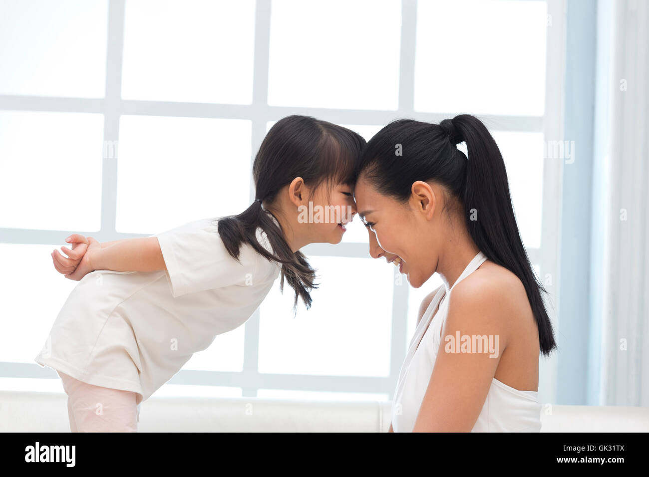 Happy mother and daughter playing on the couch - Stock Image