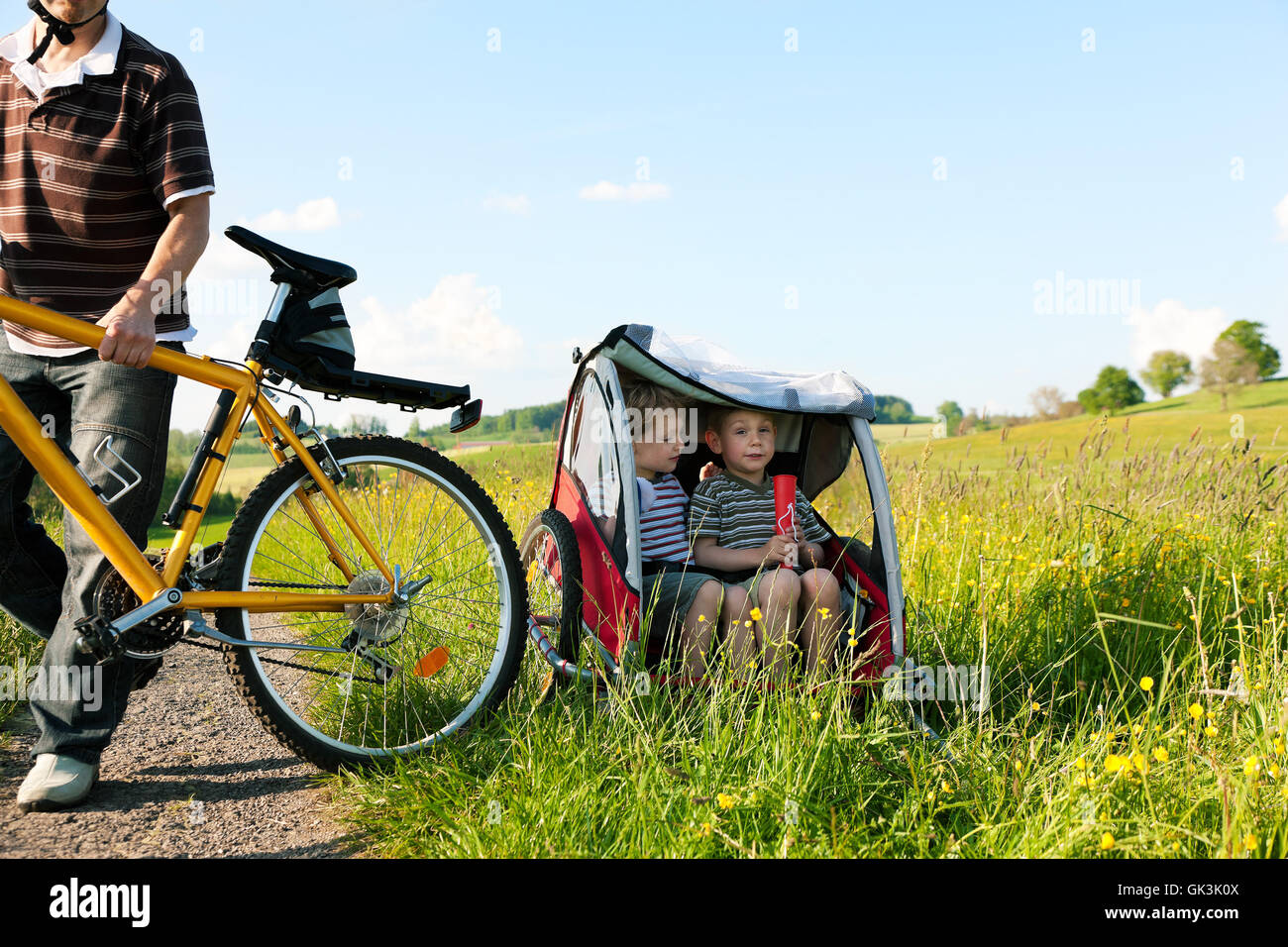 family rides a bike in the summer with trailer - Stock Image
