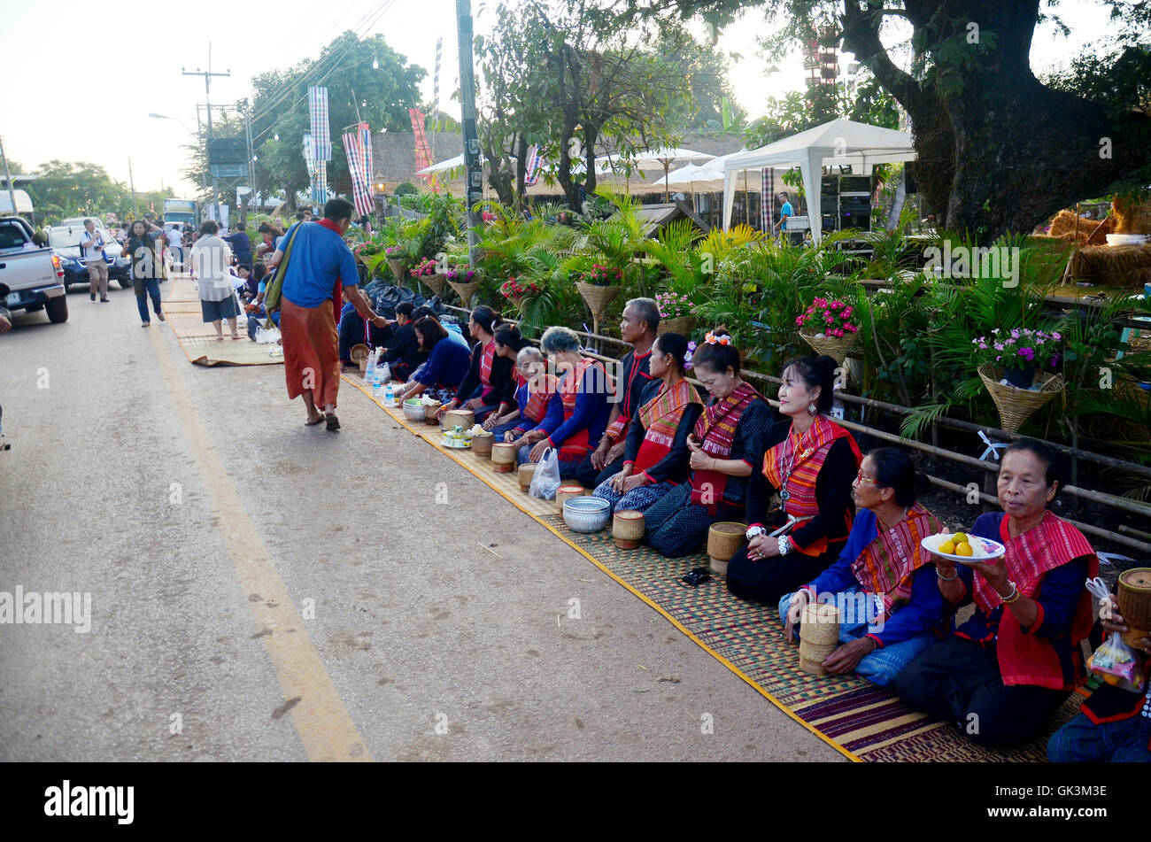 Phu tai people preparing food and almsgiving with sticky rice for put food offerings to monks procession at the Stock Photo