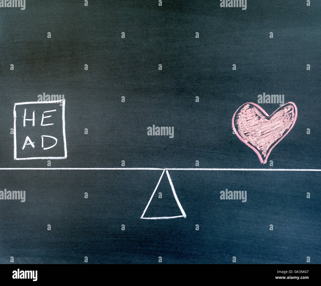 head and heart symbols drawn on a chalkboard, balance scale in equilibrium. - Stock Image