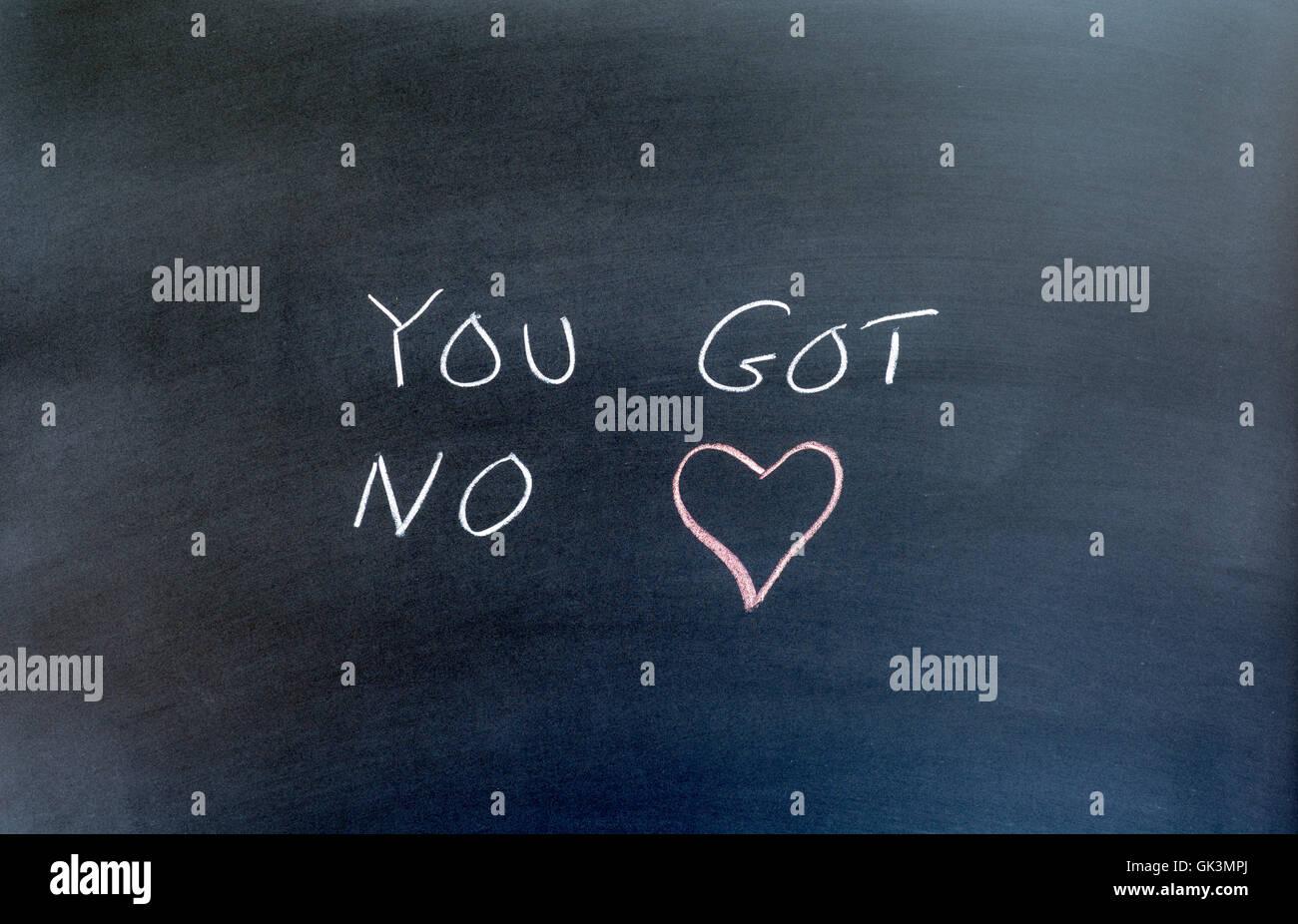 phrase 'you got no heart' written on a chalkboard. - Stock Image