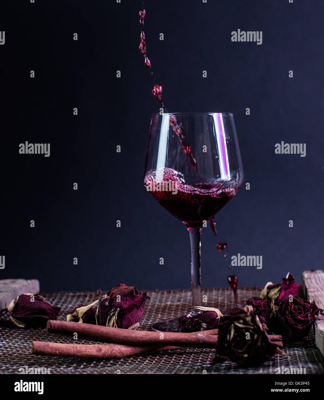 splash of red wine in to a glass - Stock Image