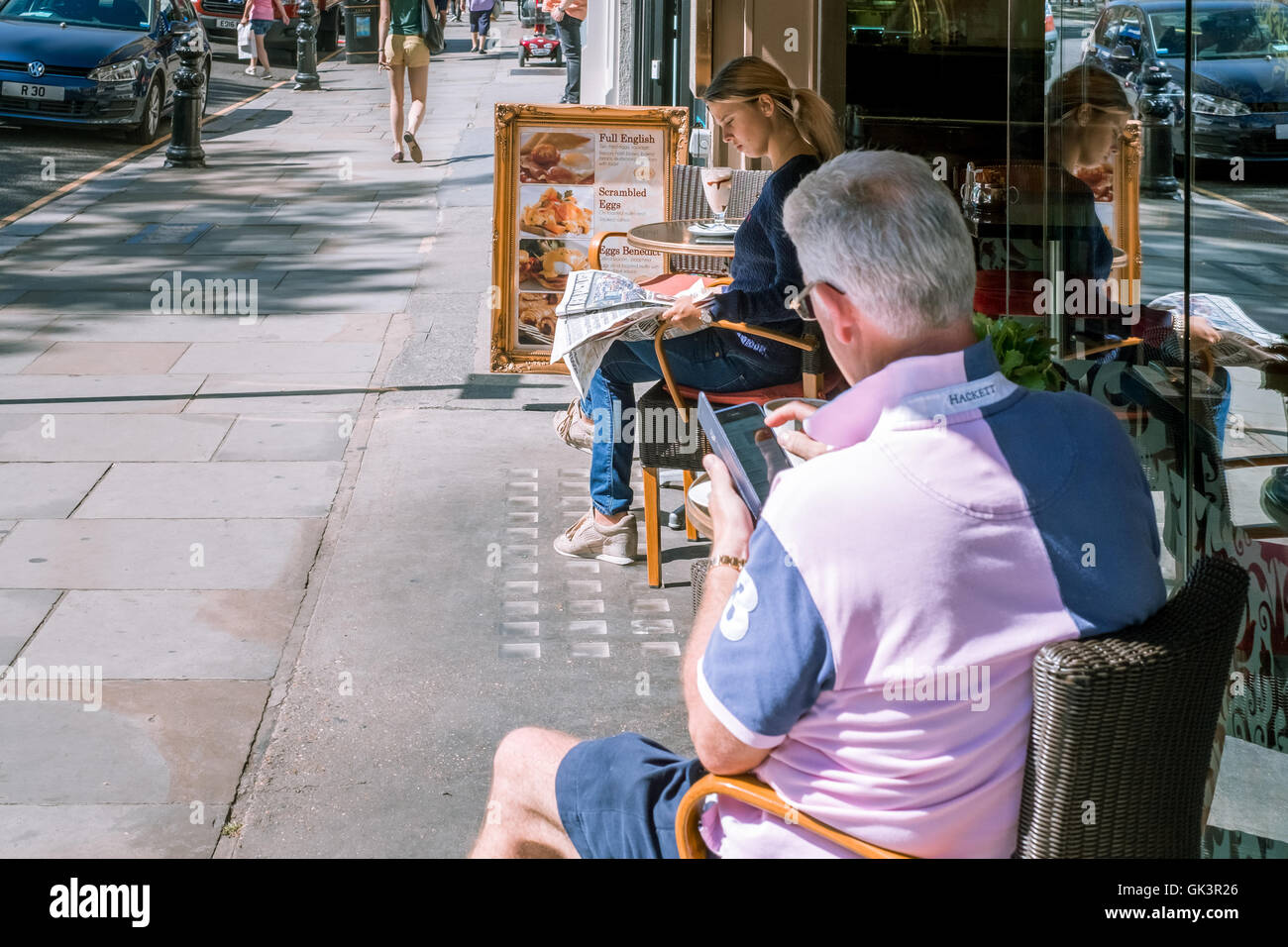 A young woman and an older man enjoying dining alfresco in London on a beautiful sunny day - 8th August 2016 - Stock Image