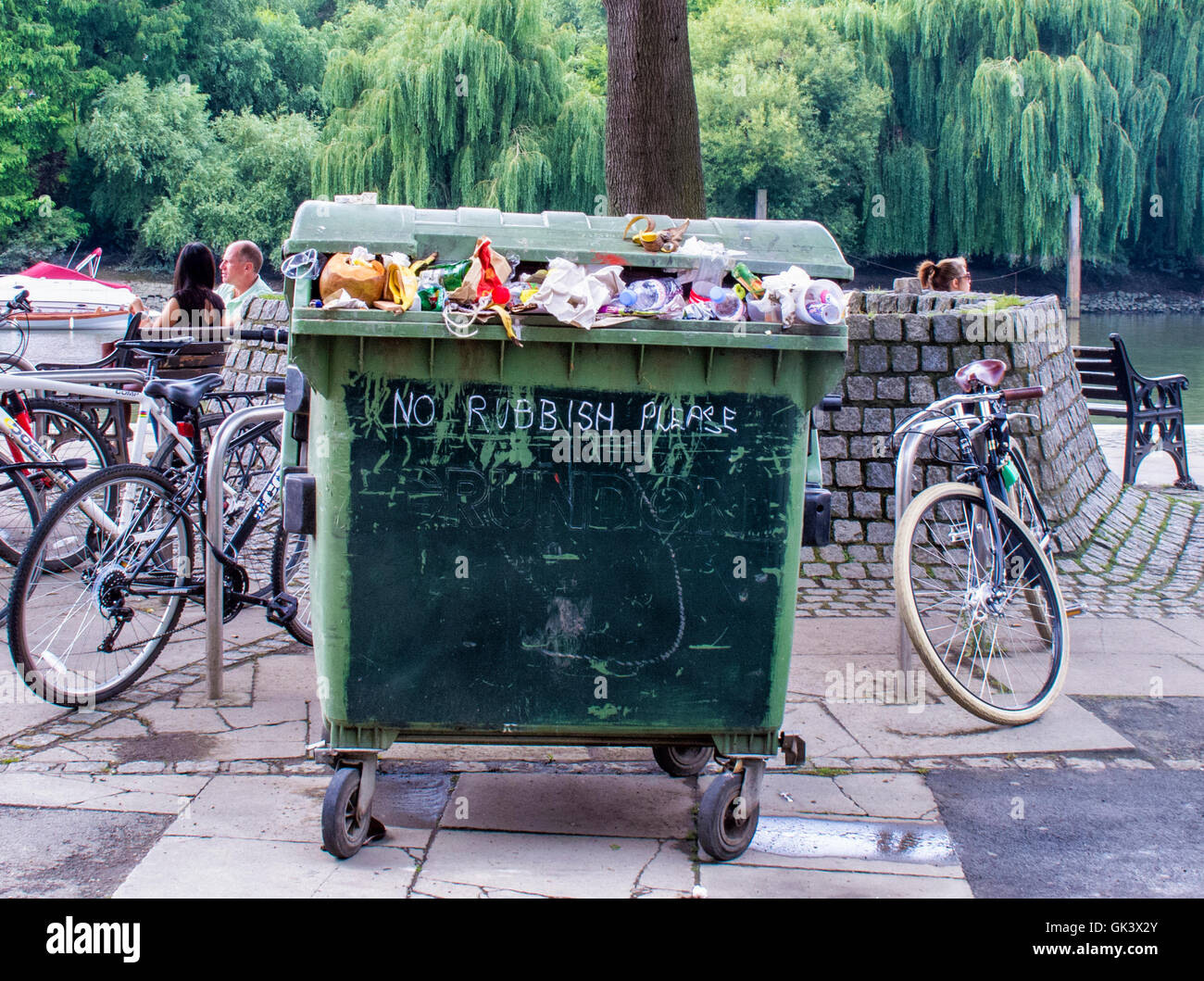 Wheely bin, overflowing trash can with 'no rubbish please' on the side Richmond upon Thames, Greater London. - Stock Image