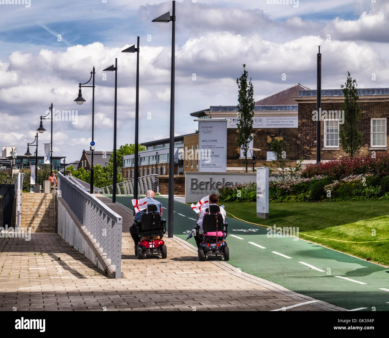 Two disabled people on mobility scooters with English Saint George flags - Thames path, London - Stock Image