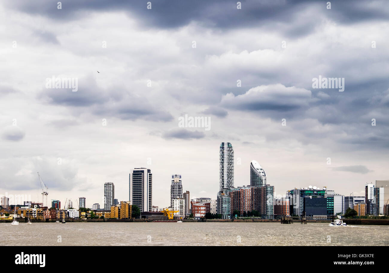 London docklands skyline - new build luxury riverside apartment buildings along the river Thames with dramatic cloudy - Stock Image