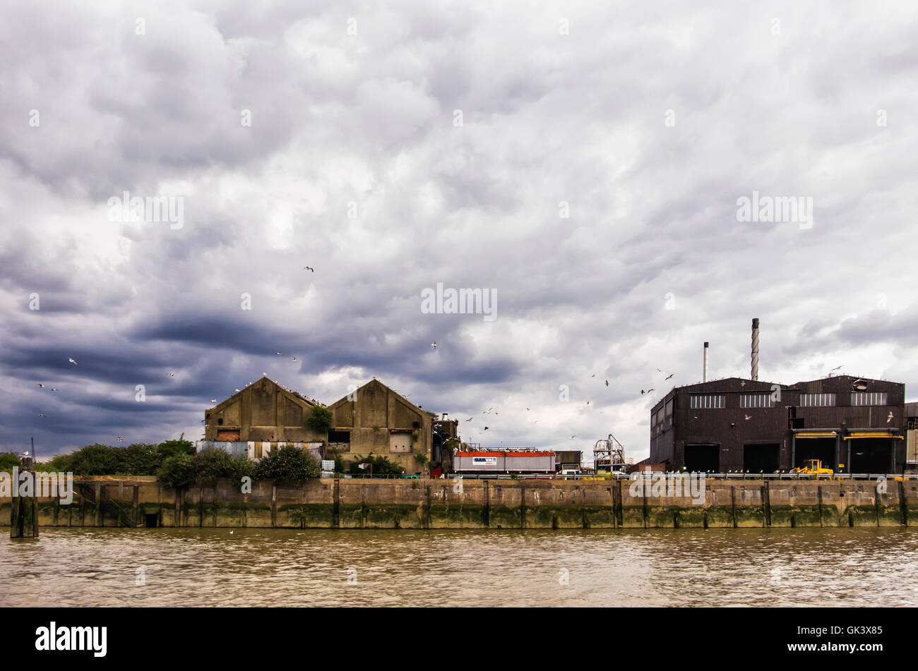 London Docklands. Old warehouse buildings along river Thames with black stormy, cloudy sky, Sivertown - Stock Image