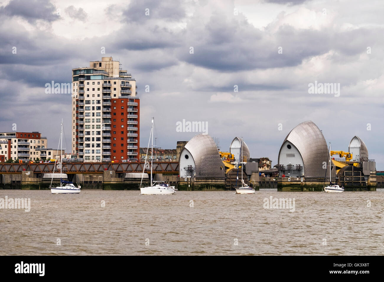 London. Yachts pass through open Thames Barrier under dramatic cloudy black sky and threatening storm clouds - Stock Image