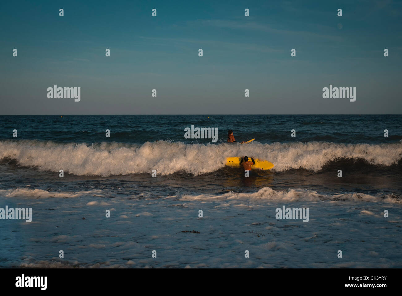 Two young surfers enjoying the late evening high tide as sun sets on Gyllyngvase Beach, Falmouth, Cornwall 15/08/16 - Stock Image