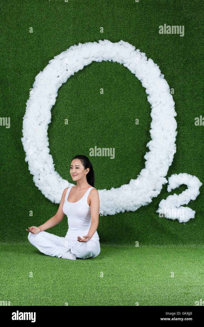 Grassland creative young women sitting on the grass - Stock Image