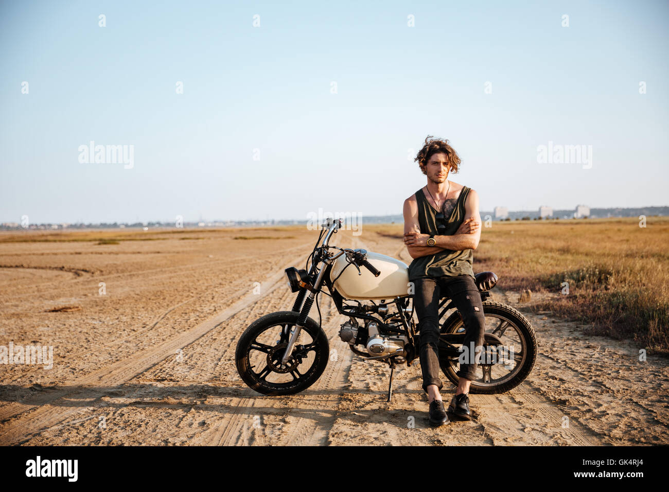 Young brutal man in black leaning on a motorcycle - Stock Image