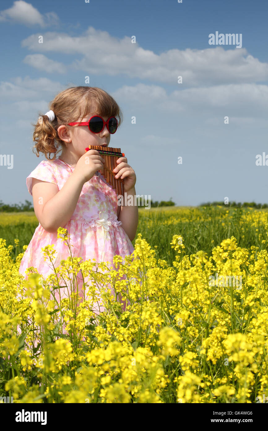 little girl standing in yellow flower field and play pan pipe - Stock Image