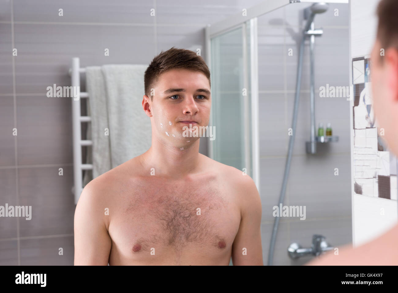 Young man with cuts on his face after bad shaving  standing in front of mirror in  the modern tiled bathroom at - Stock Image